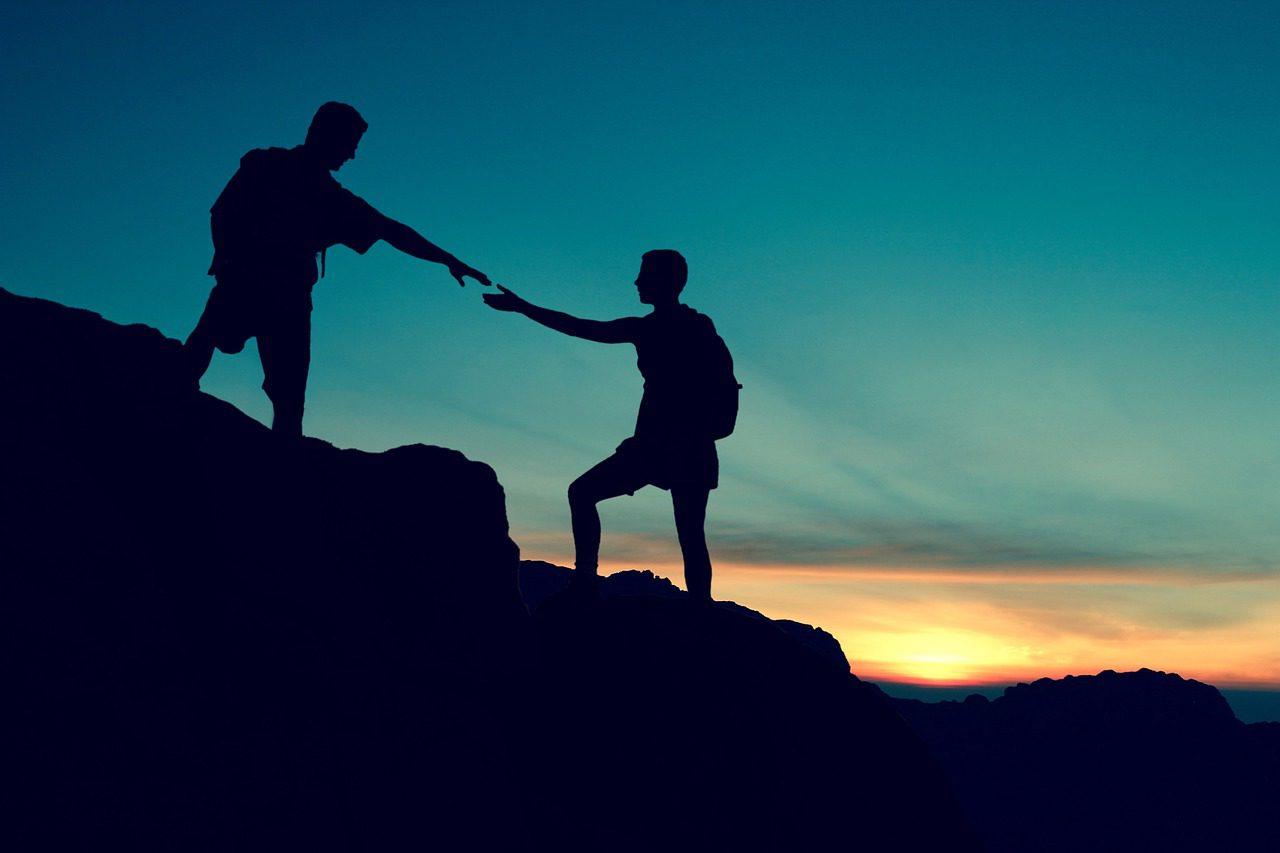 a friend lending a friend a hand while hiking