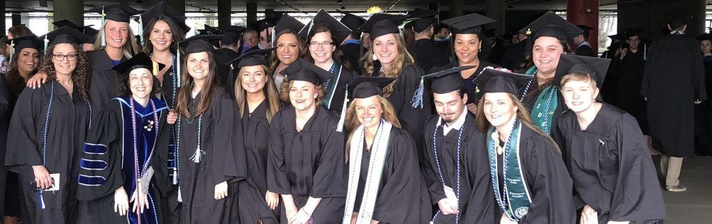 A group of students posing for a photo in their graduation gowns