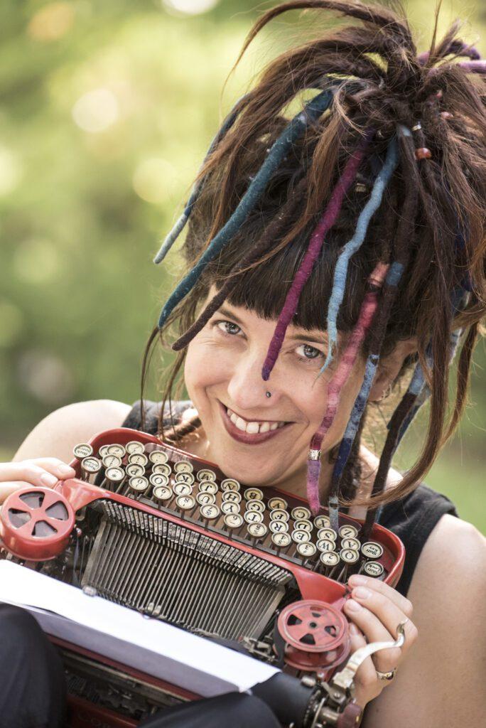 White woman with dredlocks and typewriter, smiling