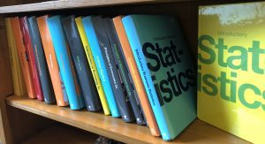 A bookshelf full of colorful openstax textbooks