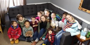 Becca Roberts posing with a group of children, after teaching them about mushrooms.