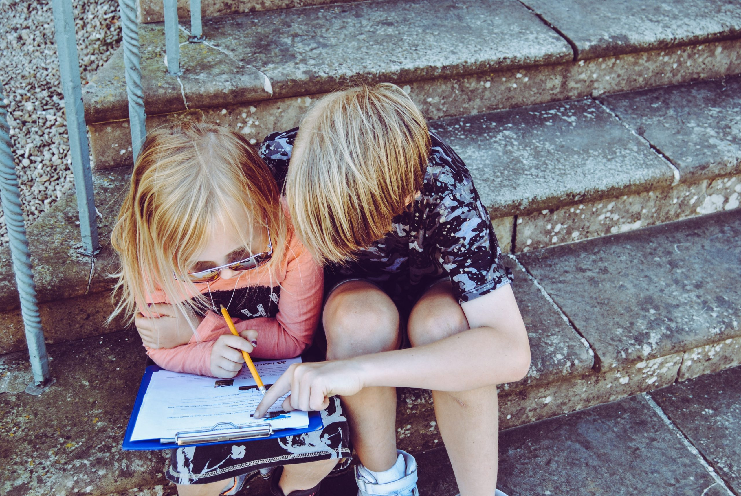 Two children sitting on cement steps examine a paper on a clipboard.