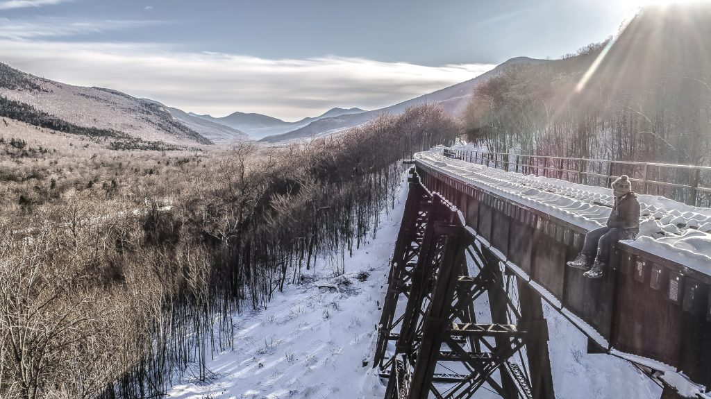 person sitting on a trestle railroad bridge in the snow, looking towards the moutains