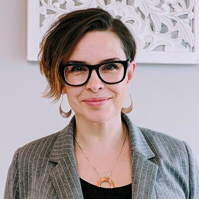 woman in glasses with short hair smiling