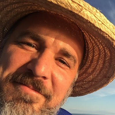 image of white man with beard in hat, smiling
