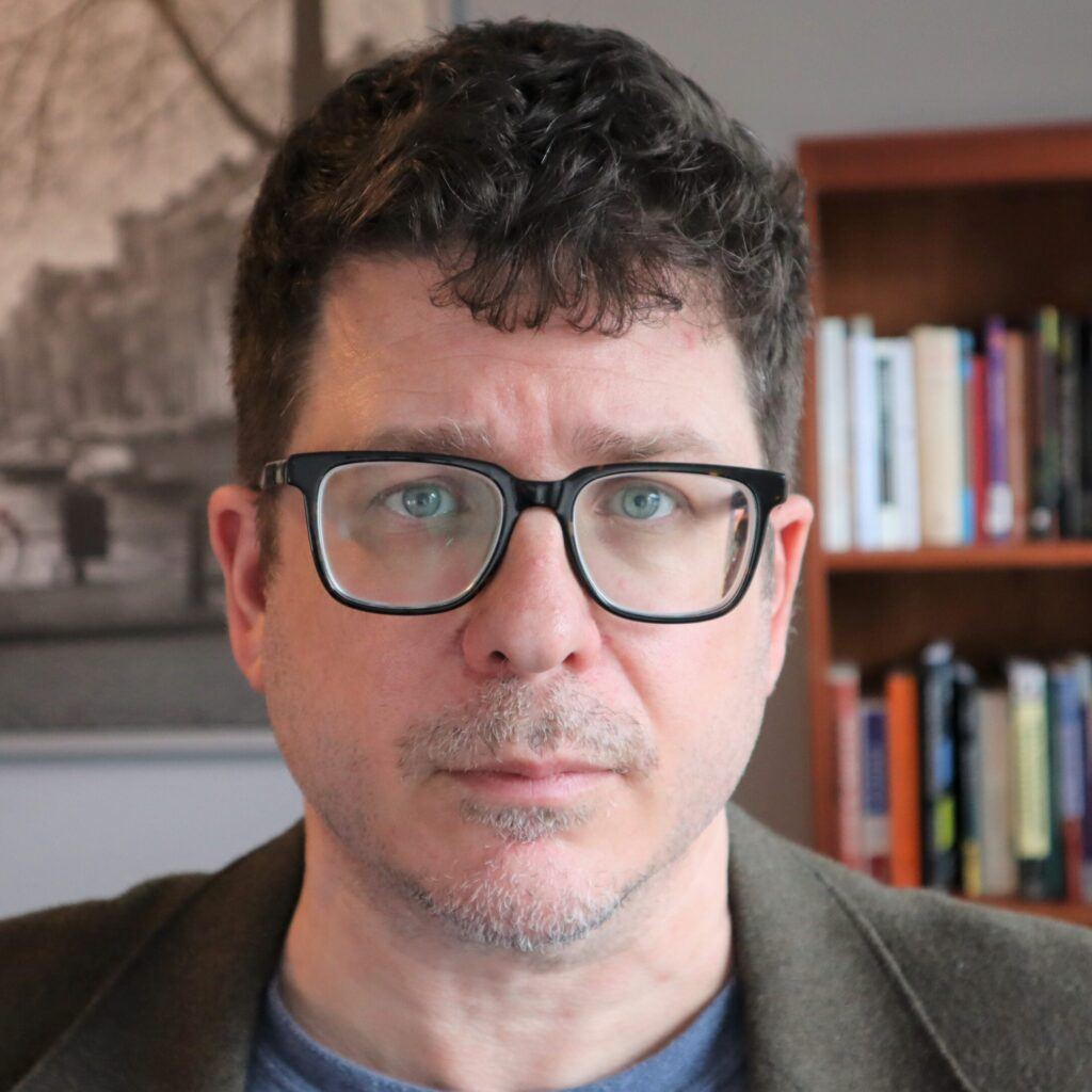 white man in glasses looking at camera