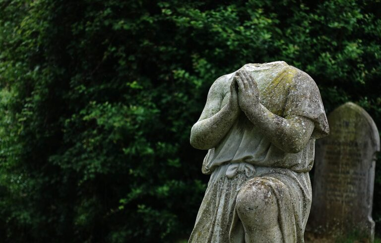 headless statue at grave
