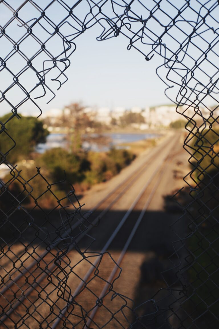 image of a broken fence with a scene beyond of a train track