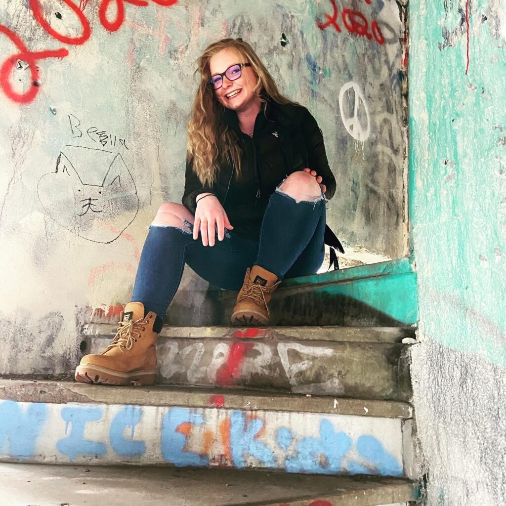 Rhiannon posing on concrete stairs in front of a wall of graffiti