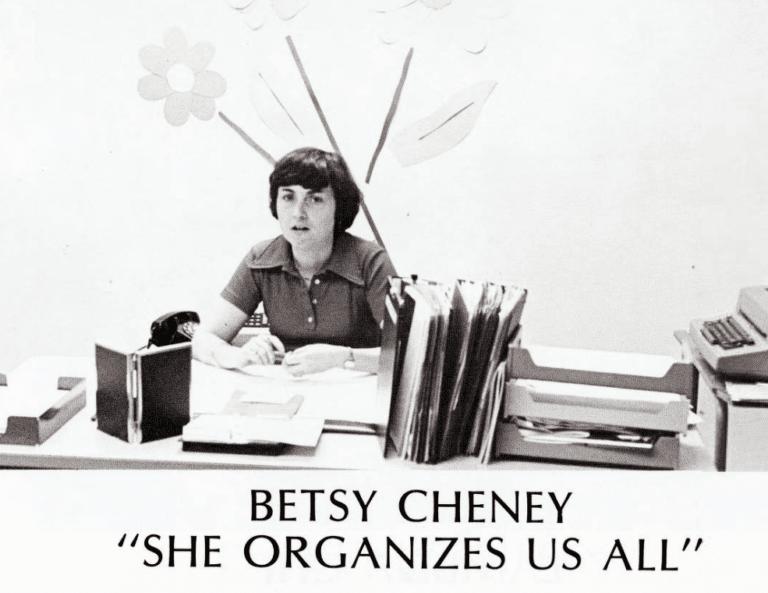 "Besty Cheney sitting at a desk, ""She organizes us all."""
